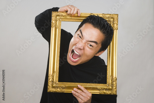 Asian man yelling through picture frame