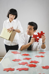 Asian woman timing man putting together puzzle