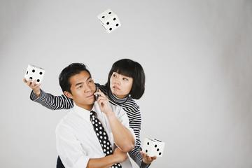 Asian woman juggling dice over man