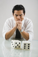 Asian man looking at dice