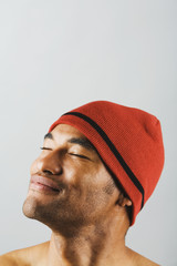 Asian man wearing hat with eyes closed