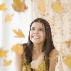 Leaves raining down on Hispanic woman
