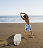 Hispanic man stretching next to surfboard
