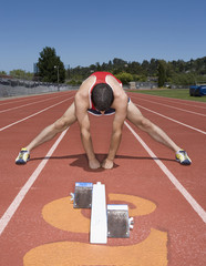 Hispanic male runner stretching on track
