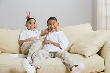 Indian brothers being silly on sofa