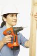 Hispanic female construction worker using drill