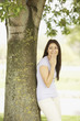 Portrait of Hispanic woman leaning against tree