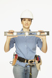 Hispanic female construction worker holding level