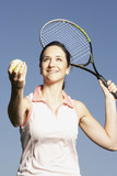 Hispanic woman serving tennis ball
