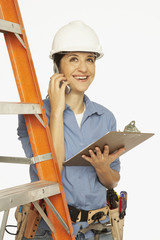 Hispanic female construction worker talking on cell phone