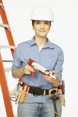 Hispanic female construction worker holding caulking gun