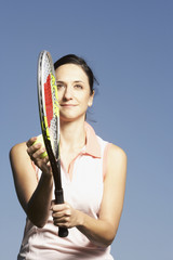 Portrait of Hispanic woman holding tennis racket