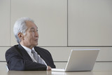 Senior Asian businessman sitting next to laptop