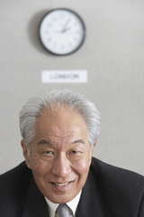 Senior Asian businessman under wall clock