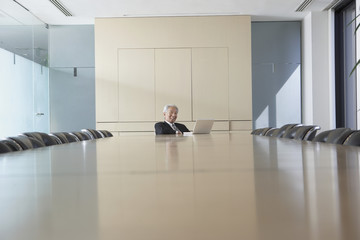 Senior Asian businessman at conference table