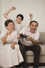 Hispanic grandparents and grandson playing video games