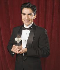 Portrait of Hispanic man holding award