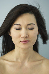 Asian woman with eyes closed