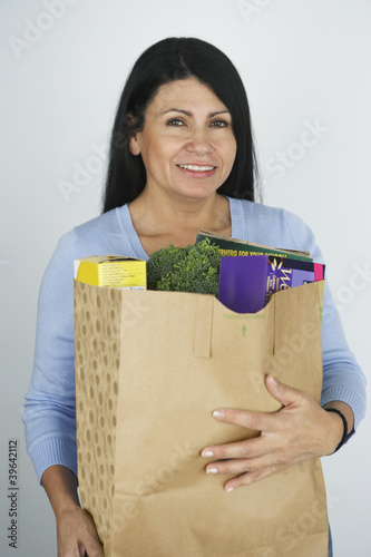 Hispanic woman carrying grocery bag