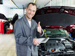 Master mechanic in a garage shows thumb up for good service
