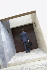 Hispanic businessman standing at doorway