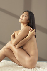 Nude Asian woman covering breasts with arms