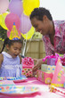 African girl receiving gift at birthday party