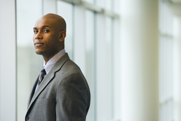 African businessman standing next to window