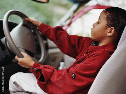 African boy pretending to drive car