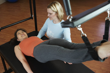 Asian woman exercising with personal trainer