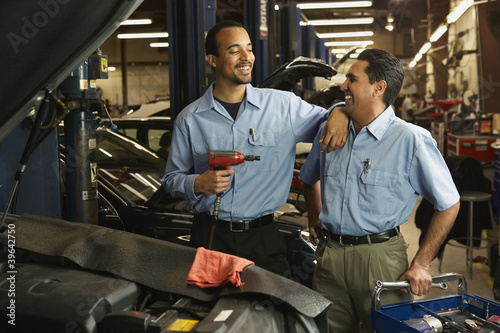 Multi-ethnic male auto mechanics in shop