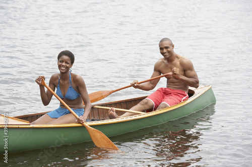 African couple paddling canoe