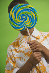 African boy holding big lollipop over face