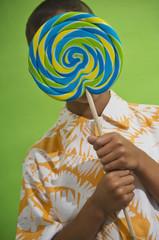 African boy holding big lollipop over face