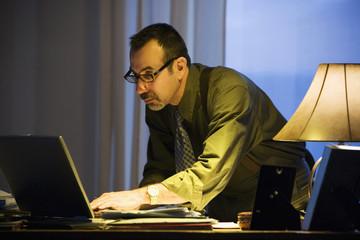 Hispanic businessman typing on laptop