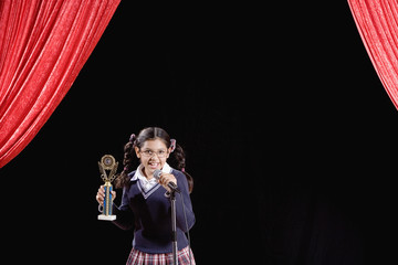 Hispanic girl holding trophy on stage