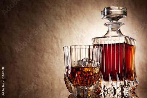 glass and decanter of brandy on a old stone background