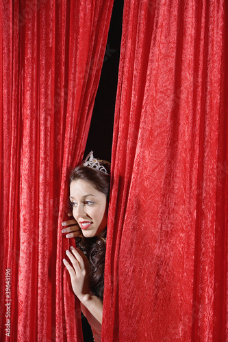 Hispanic beauty queen peeking through curtains