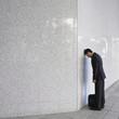Businessman leaning head on wall