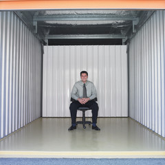 Businessman sitting in empty storage space