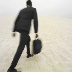 African businessman walking on beach