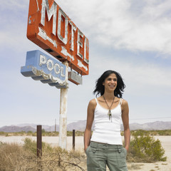 Hispanic woman next to motel sign on beach