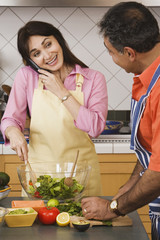 Middle-aged Hispanic couple preparing food in kitchen