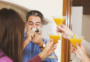 Middle-aged Hispanic man taking photograph of friends