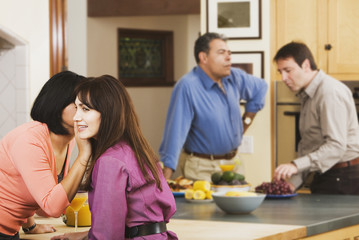 Two middle-aged couples in kitchen