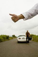 Man holding out thumb for hitchhiking