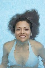 Hispanic woman floating in swimming pool