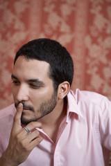 Hispanic man thinking with finger on lip