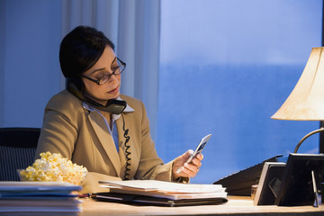 Hispanic businesswoman using telephone and cell phone