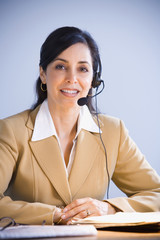 Hispanic businesswoman wearing headset